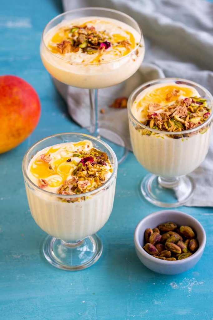 Three glasses of mango mousse on a blue background. The mango mousse cups are garnished with mango puree, pistachios and rose petals. On the top right corner is a mango, and on the bottom right corner is a small bowl of pistachios.