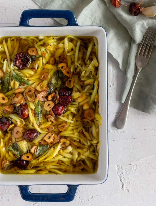 A blue dish with white inside on a white backdrop. Inside the dish is grated mango pickle or rishte ka achar. Next to the dish is a fork, whole red chilies and garlic on top of a green napkin.