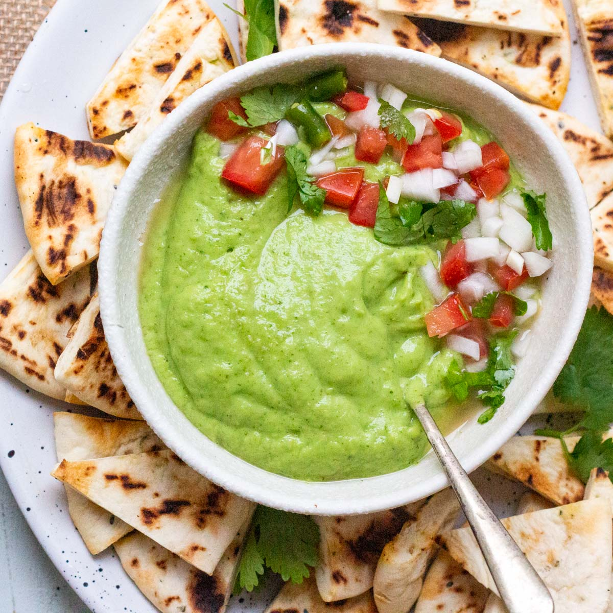 A plate of toasted pita chips. In the middle of the plate is a bowl of avocado green chutney with a spoon in it, and garnished with chopped coriander, tomatoes and onion.