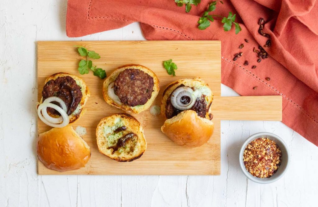 Three chapli kabab sliders on a wooden board. On the top is a rust colored napkin with dried pomegranate seeds on top of it, and coriander leaves. On the bottom right is a small bowl of red chili flakes.
