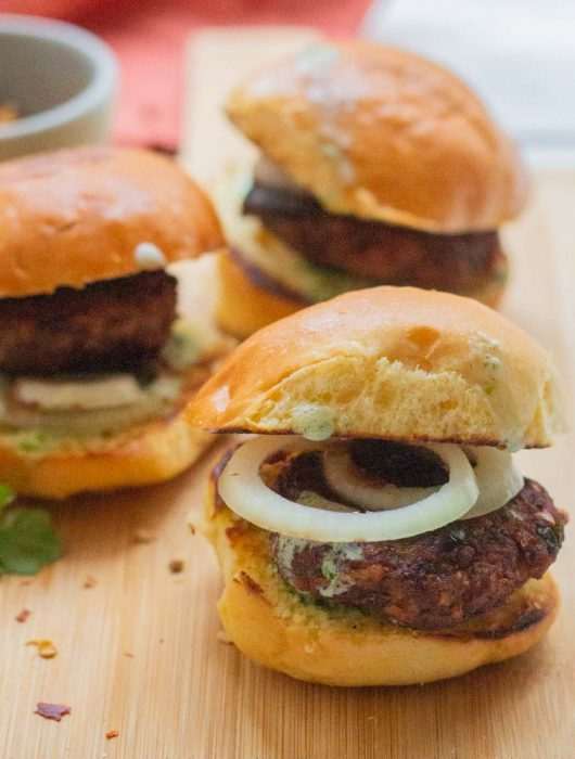 Three chapli kabab sliders on a wooden board with a rust colored napkin in the background and a small bowl of red chili flakes.
