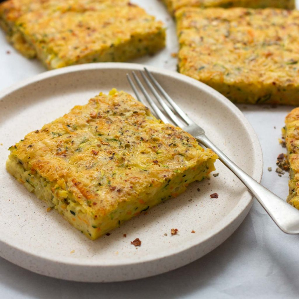 A piece of zucchini slice on a white plate with a fork next to it. On the right side are two more pieces of zucchini slice.