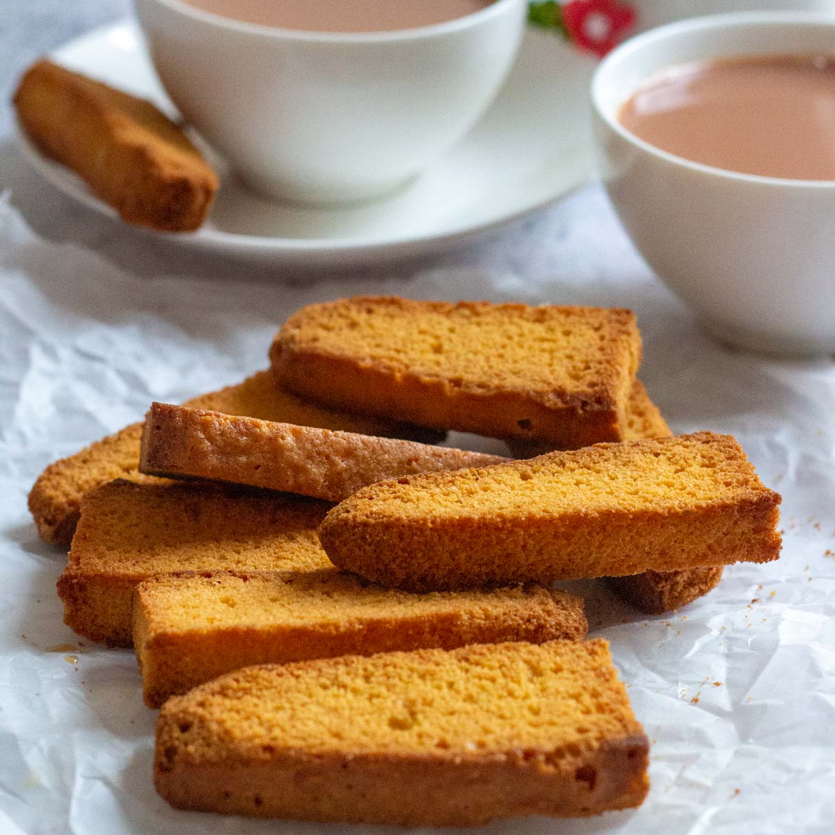 A pile of cake rusk on parchment paper. At the back are two cups of tea, and one of the cups of tea has a cake rusk placed on the saucer.
