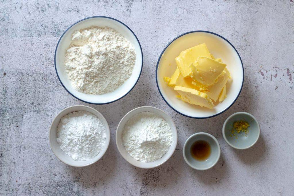 Ingredients for lemon sandwich cookies laid out in bowls - flour, butter, icing sugar, cornflour, vanilla essence and lemon zest.