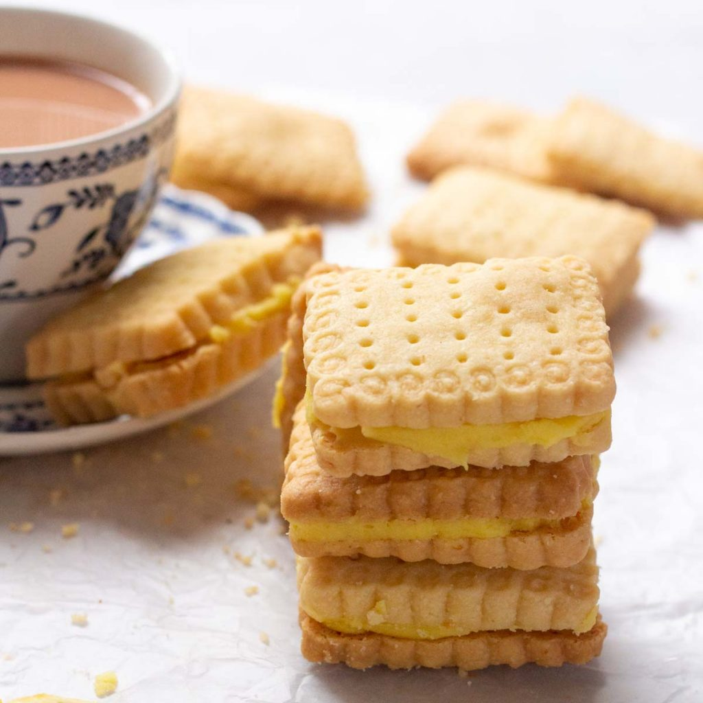 A stack of three lemon sandwich cookies with lemon buttercream filling. On the back in the top left corner is a cup of tea with a saucer on which a biscuit is kept. In the background are a few lemon sandwich cookies as well.