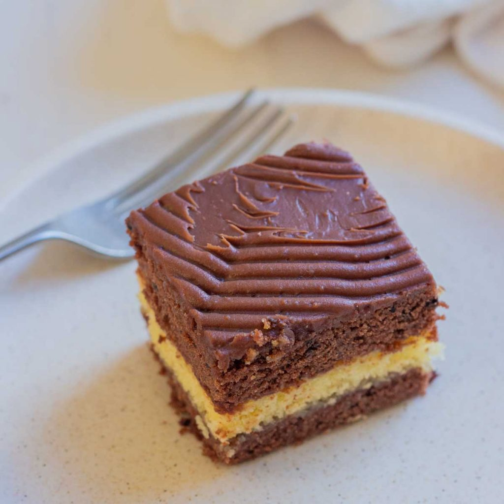 A slice of chocolate vanilla cake on a plate with a fork placed behind it.