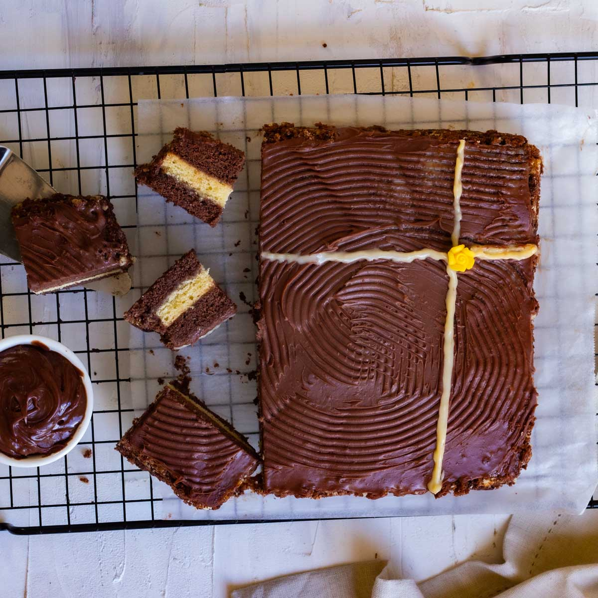 A top down shot of a chocolate vanilla cake. The cake is cut in half, and placed on parchment paper on top of a baking rack. There are 4 cake slices along with a bowl of chocolate ganache placed in front of the cake.